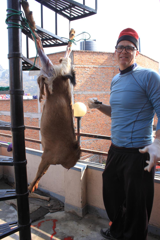 Joel preparing the goat for dinner