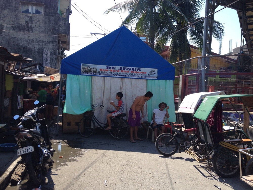 At the side of one of the basketballs courts on Bangus St, Navotas, a tent is erected to host a baptism. As I travel around on Sunday, I notice tent are a popular business. People rent tents for special events likely because their homes are too small to accommodate guests, but possibly because they are also public events.
