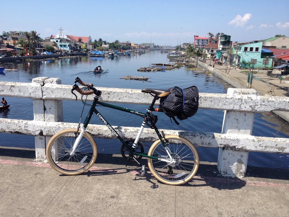 Crossing the Navotas River on the C-4 bridge. Both sides of the river have wide easements and are easy to bike. There are only two bridges connecting Navotas and Malabon, the C-4 bridge and the Estrella bridge. Fishing boats are abundant and it's possible to pay them for crossing, but I did not see commuter boats which could bring you the length of the river from one city to another. This requires further investigation.