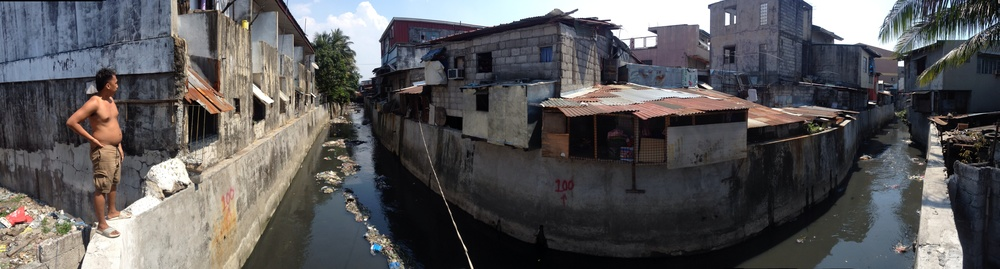 A man shows me the estero behind the Maypajo Market in Caloocan (South). The estero is lined with informal settlements that have been barricaded behind concrete walls. As we stand there I see an invisible hand throw a bag of trash from a house into the river.