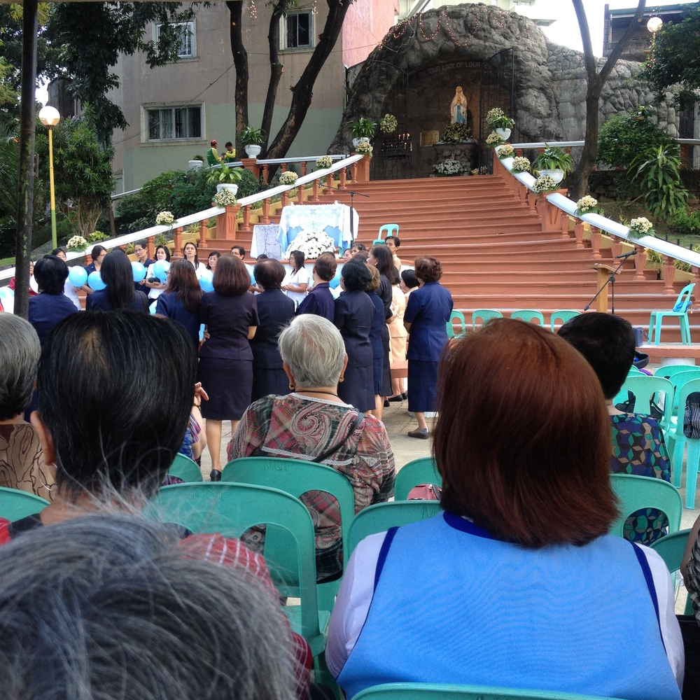 The Feast of Our Lady Lourdes is celebrated with an afternoon mass in front of a large grotto along the river.