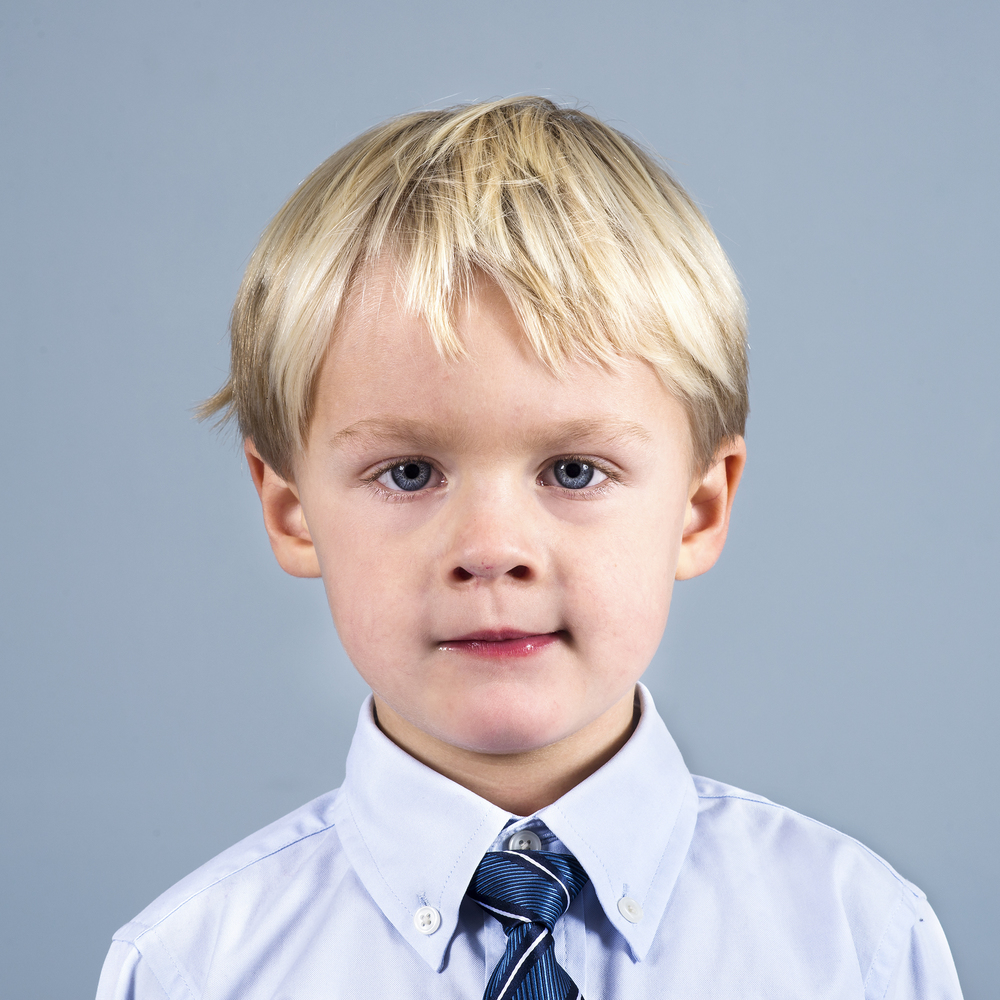 Sometimes the kid just won't smile, but that's okay, his personality comes out in this pseudo-formal portrait against a blank wall. It was his idea to wear a tie, after all.