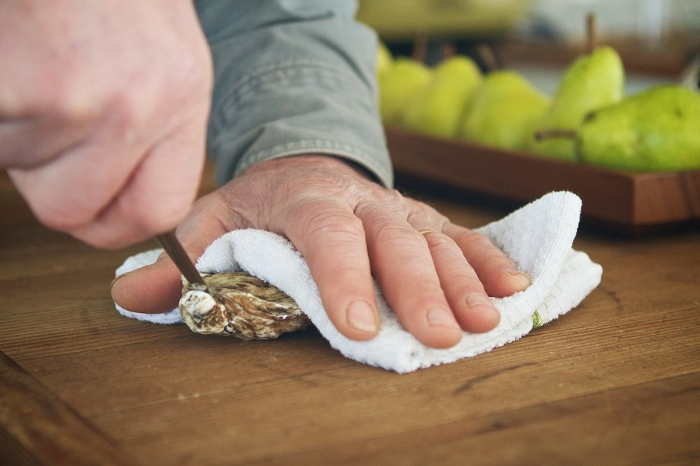 Hold the oyster firmly under the towel on a cutting board or table top, cup side down. Wiggle your knife between the two shells at the tip of the oyster as shown in the picture.