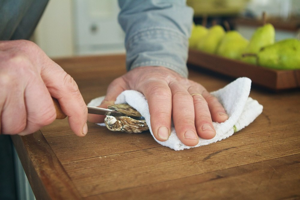 By carefully pushing the knife down into the oyster while simultaneously applying a twisting  force (like turning a set of keys) you should be able to pop open the hinge.  This will be apparent when you can slide the knife into the oyster.