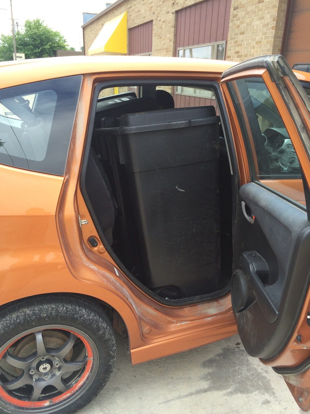 That's a pair of 50 gallon garbage cans standing upright in the back of the car...