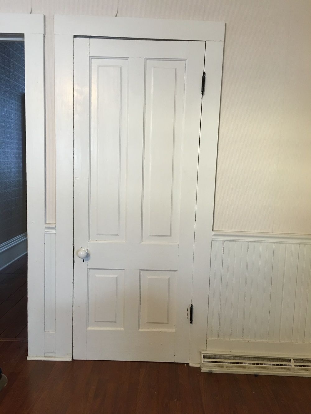 The flat, simple woodwork around this (poorly hung) kitchen door is consistent with what can be found throughout the back side of the house, both upstairs and down...