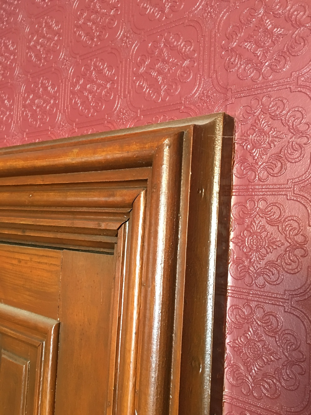 This closeup of the dining room door shows that, while it is also built out in a somewhat ornate fashion, it does not continue to radiate outward beyond the edge of the frame.
