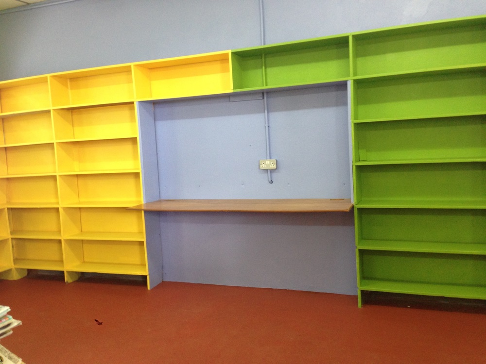 Yellow, green and blue shelves correspond to books that are for beginning, intermediate, and advanced readers. The colors come from the three house teams in the school, named after St. Lucian trees: Leuecaena, Caribbean Pine, and Blue Mahoe.