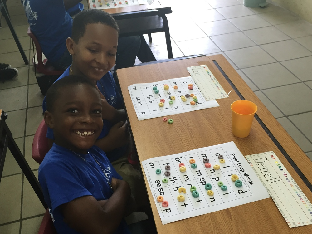 Derrell and Lee spelling Froot Loop words in Lauren's class. (Had to use generic fruit circles because Foot Loops are too expensive here.)