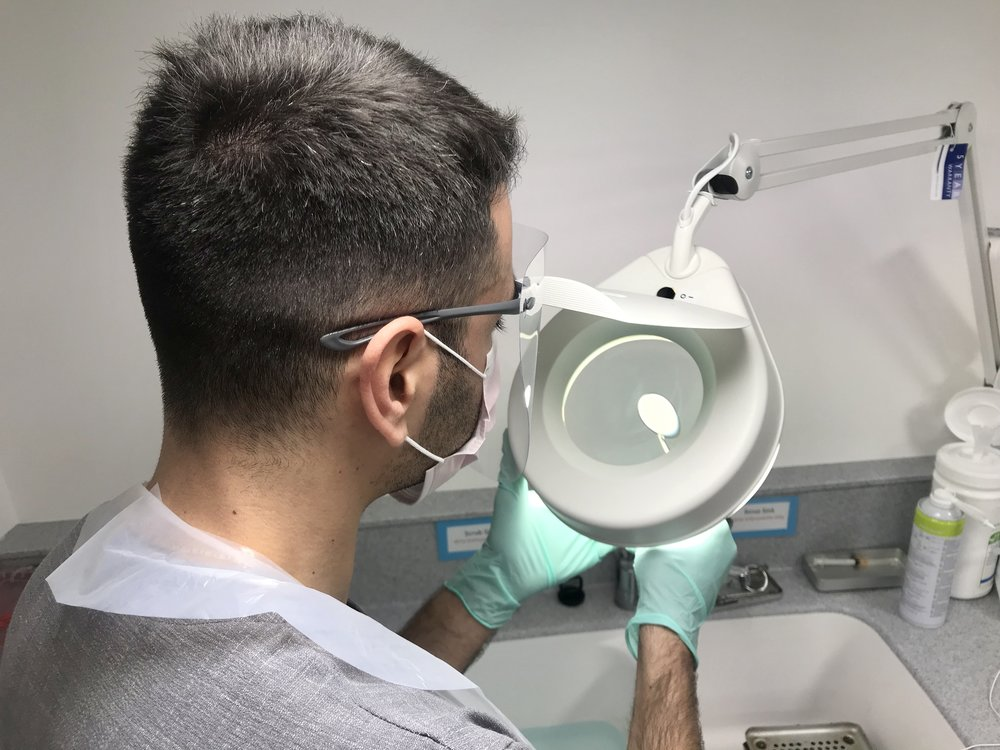 Checking dental instruments under the illuminated magnifying glass