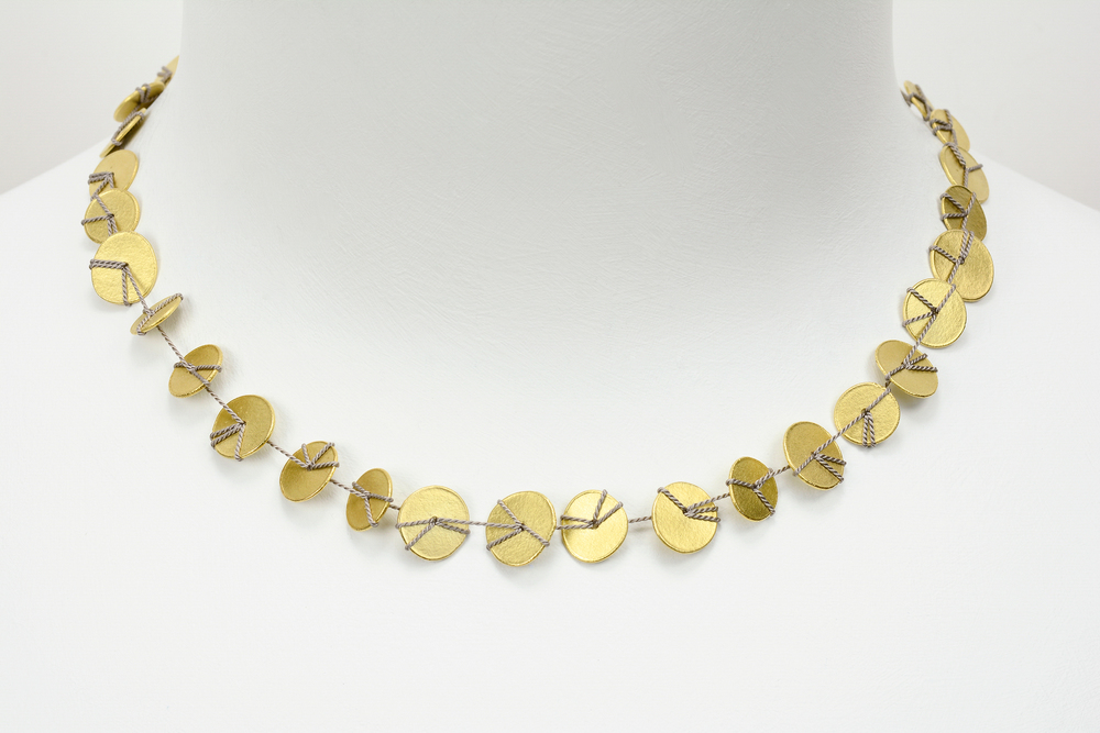 gold disc necklace . 18ky gold and silk cord - 4000.00