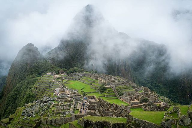 The ruins of Machu Picchu reveal themselves from the clouds after an April rain.  Just behind mountain Huyana Picchu peeks through through mist with it's iconic shape.  Have you been here, or is it on your bucket list?