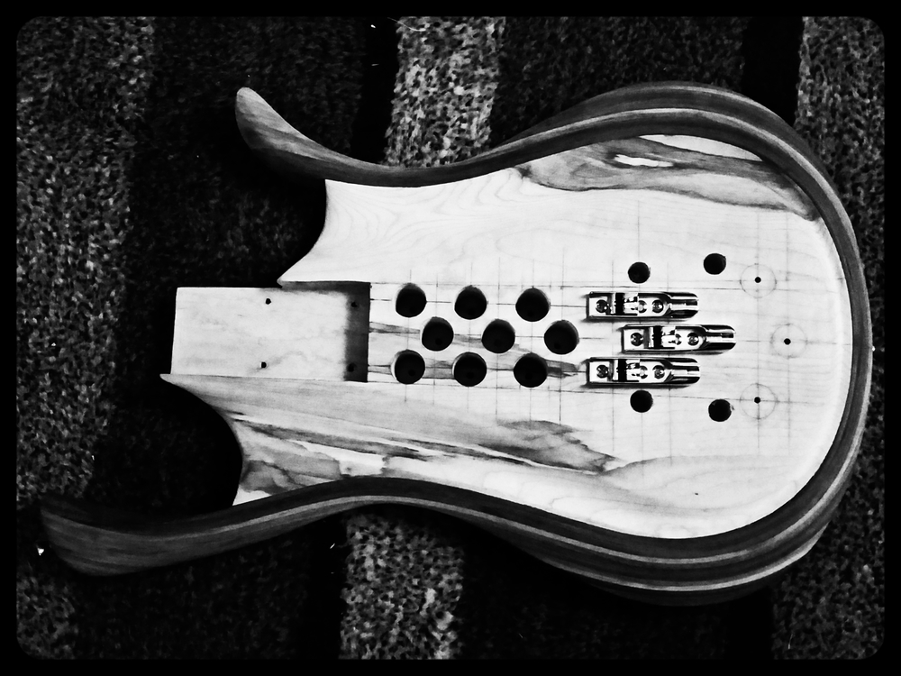 Siriena is an experimental 3 string machine in the works.  Her body is multiple layers of bent walnut strips around a figured maple core.  Check back in a few weeks to she how she's shaping up.