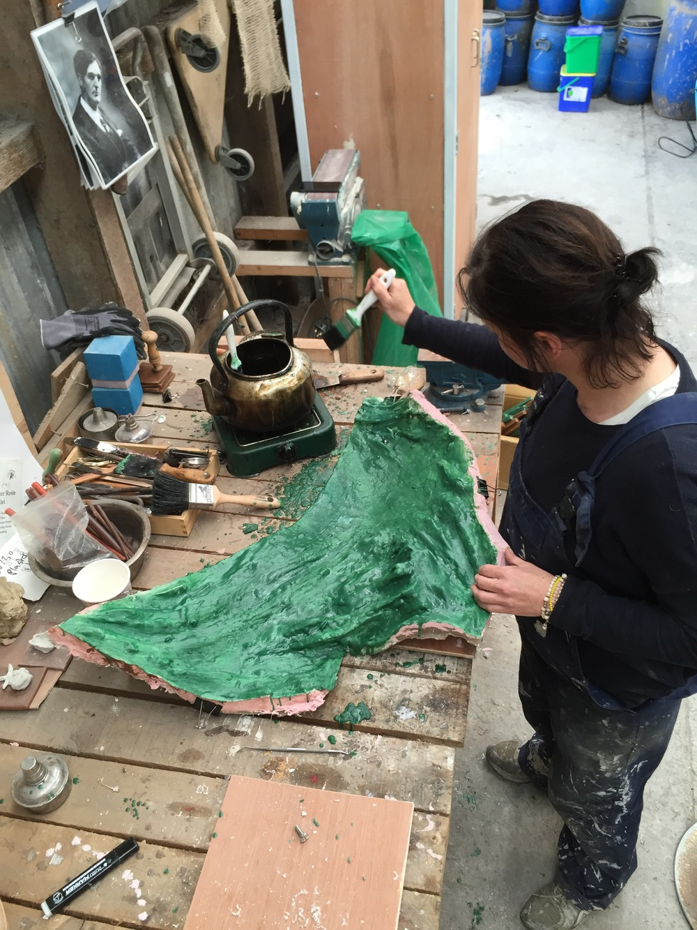 Karen is brushing molten foundry wax into a mould section. Note the photo of a young William Conor on the wall...