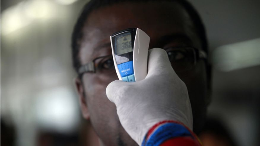 A health worker takes a passenger's temperature with an infrared digital laser thermometer at the Felix Houphouet Boigny international airport in Abidjan August 13, 2014. Ivory Coast on Monday banned air travellers from Guinea, Liberia and Sierra Leone, the three countries worst-hit by the Ebola outbreak, and ordered its flagship carrier Air Cote d'Ivoire to cease flights to and from them. Ivory Coast has not registered any cases but is seen as vulnerable given its shared borders with Guinea and Liberia. REUTERS/Luc Gnago