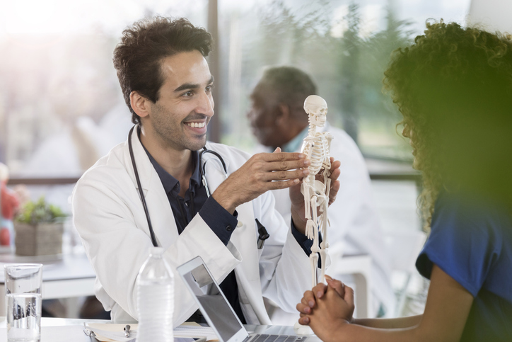 A smiling mid adult male doctor sits at a table with an unrecognizable coworker.  He uses a human skeletal model as a visual aid during a discussion.