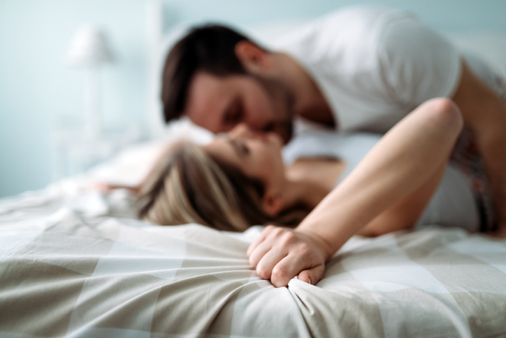 Portrait of young attractive loving couple in bedroom
