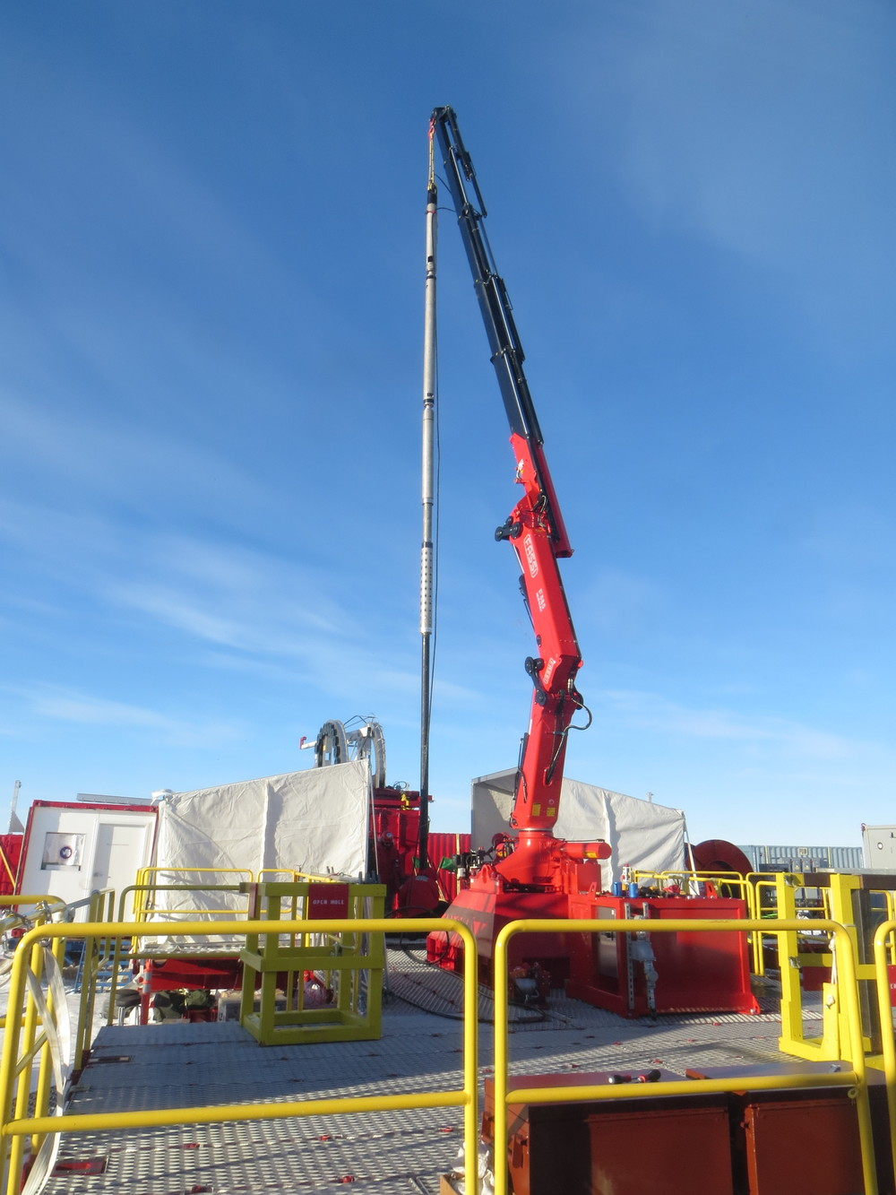 A crane lifts a large instrument to prepare it for its trip down the borehole. PHOTO BY TRISTA VICK-MAJORS