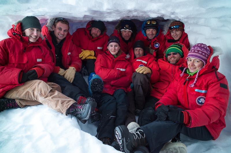 "The microbiology team in the ""ice cave freezer,"" a pit dug into the snow and ice in which samples were kept. PHOTO BY J.T. THOMAS"