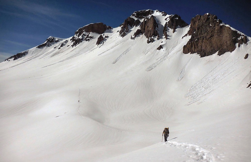 A Continental Divide Trail Hiker pushes through a snowfield in the South San Juan Wilderness.