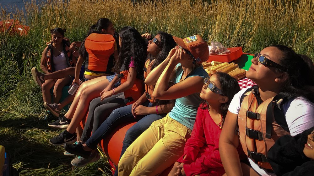 STUDENTS WATCH THE BEGINNING OF THE 2017 SOLAR ECLIPSE ON THE NORTH FORK OF THE PAYETTE RIVER IN IDAHO. (PHOTO COURTESY KAYLA BORDELON)