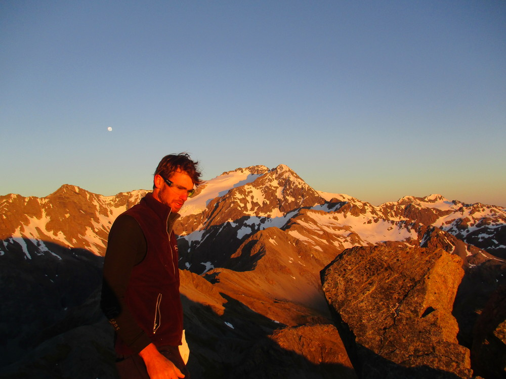 Dawn on Avalanche peak, Carl waking up from our bivvy with Mount Rolleston 2275m behind