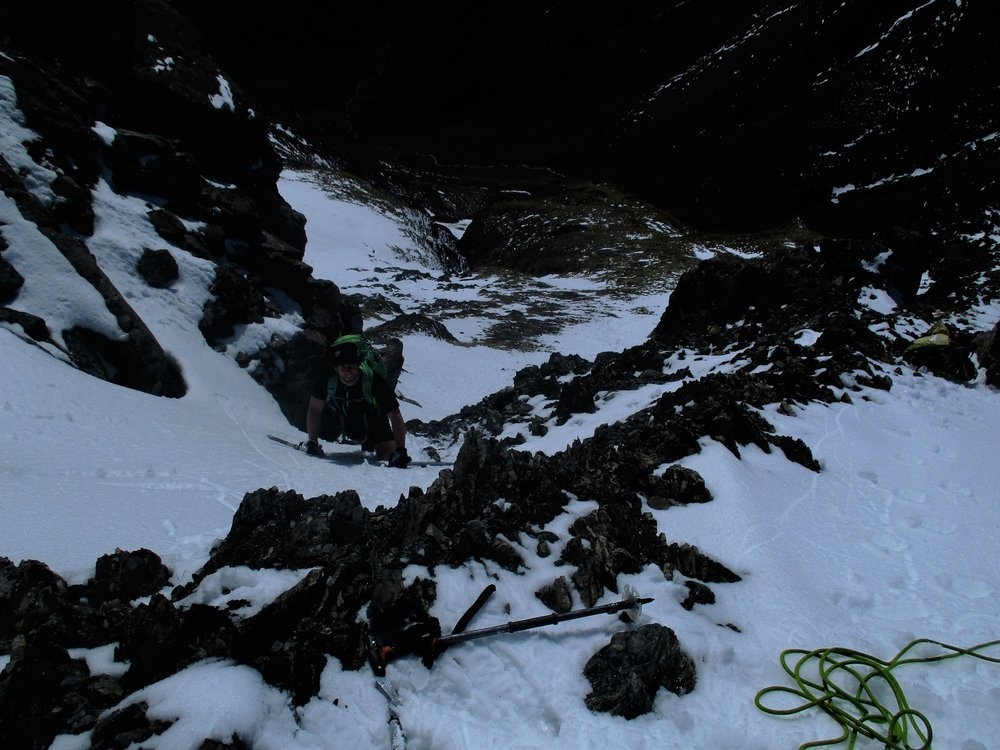 Brent climbing a steep snow gully