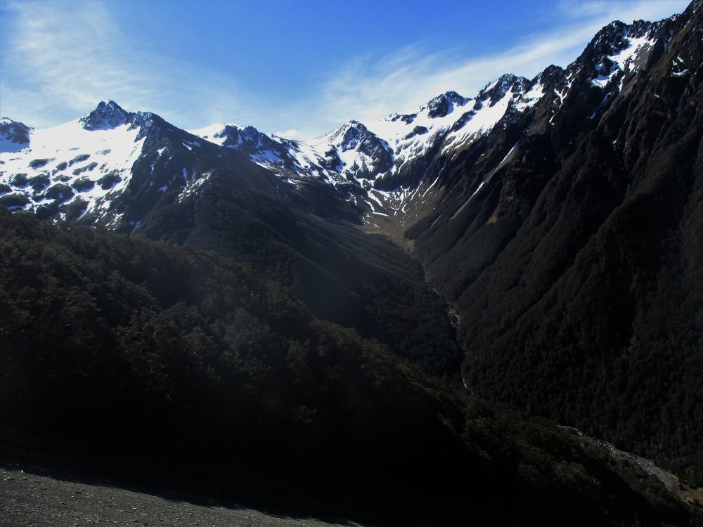 Iconic New Zealand Mountains scene , river below , than steep forest gullies leading up to the snow.