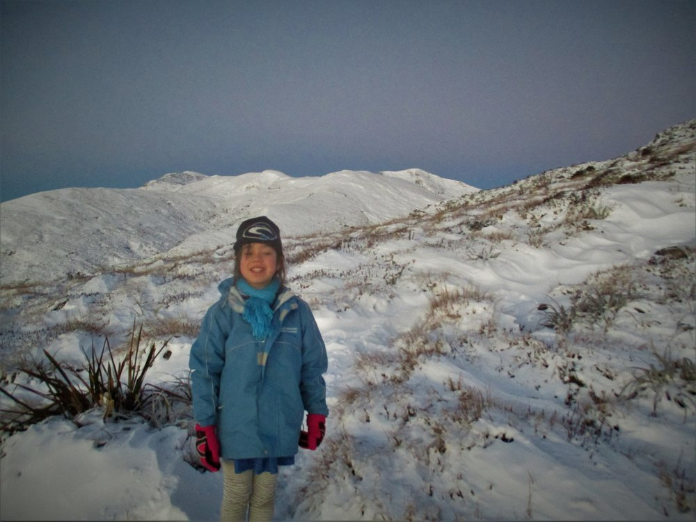 Isabelle on Mt Arthur at dawn , catching the first snowfall of the year.