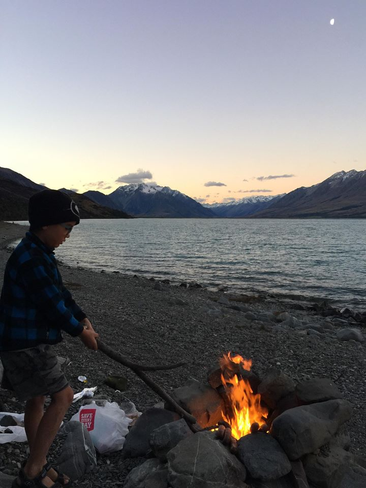 Leo cooking Kumaras (New  Zealand sweet potatoes)  and sausages while camping
