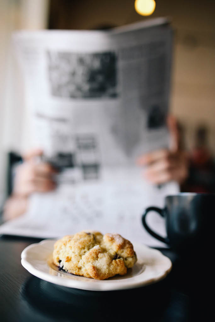 In this photo we see how the fun thing (the delicious scone) can be in focus, even while the big serious horrible thing (the news) is an important, grounding feature.  I am giving everyone permission to think about social enterprise this way.