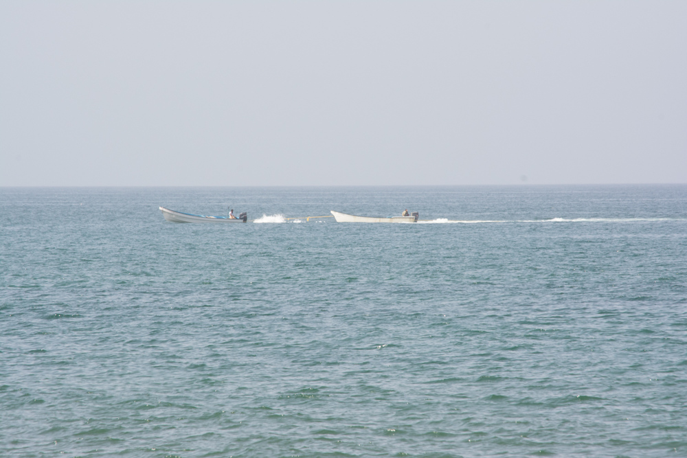 Two boats pointing left with their engines roaring, but traveling right.