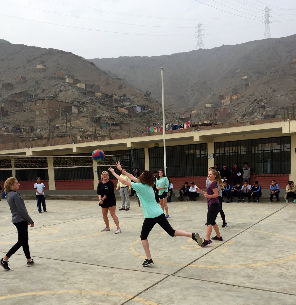 A friendly volleyball match with local students outside of Lima after a morning of service.