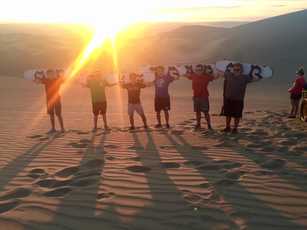 Sandboarding under the sunset in the dunes of Ica south of Lima!