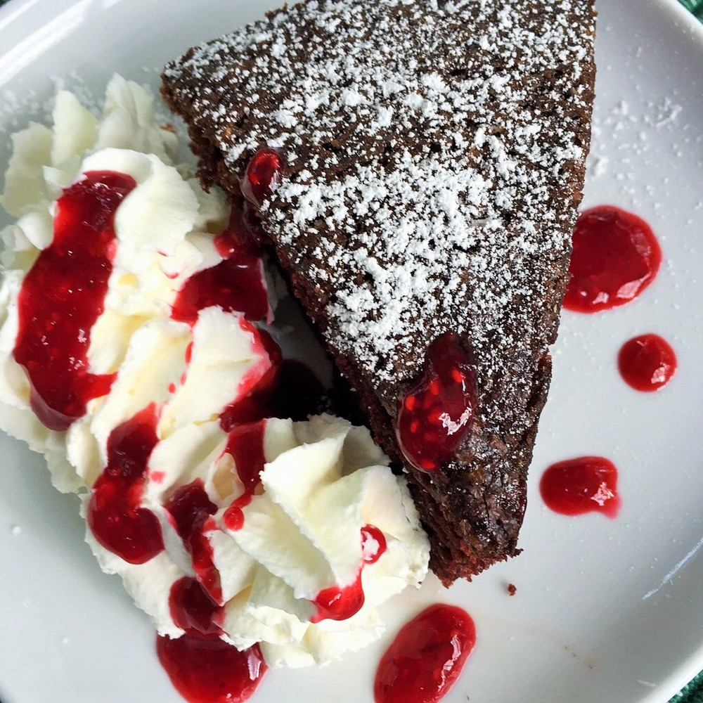 Strawberry sauce on whipped cream with chocolate almond cake