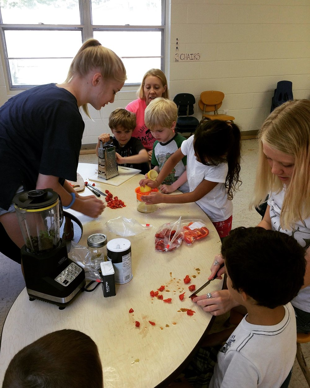 Youth help preschool children at Children's Learning Center cut veggies and make basil pesto.