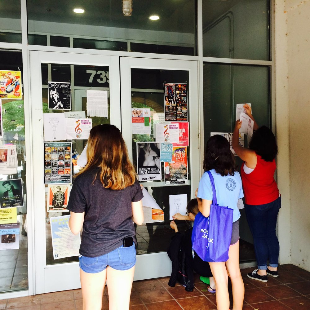 Youth flyer downtown Lawrence with anti-harassment flyers they created themselves