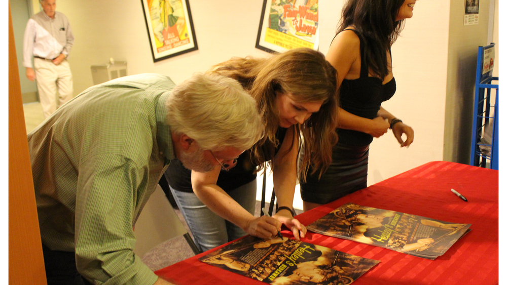 Cristie Healey and Colin Bray signing posters after the screening of Healey's Hideaway.