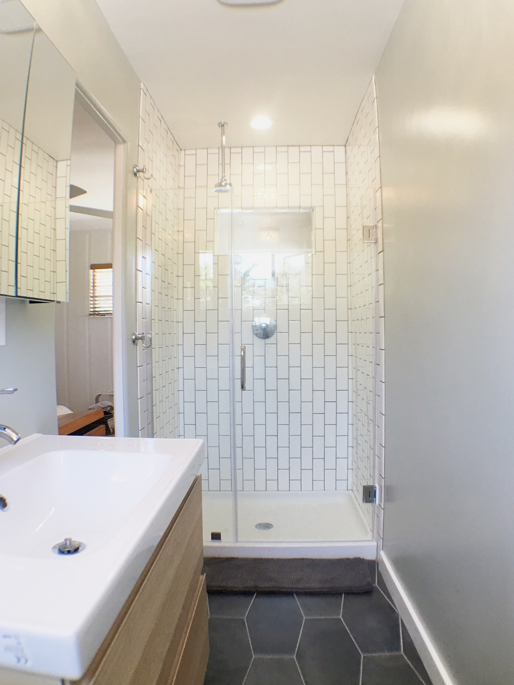 Drum roll, please. Here is my new shower! We did it super basic with white subway tile. Grout is  Delorean Gray . We turned them on their sides, just for something different.