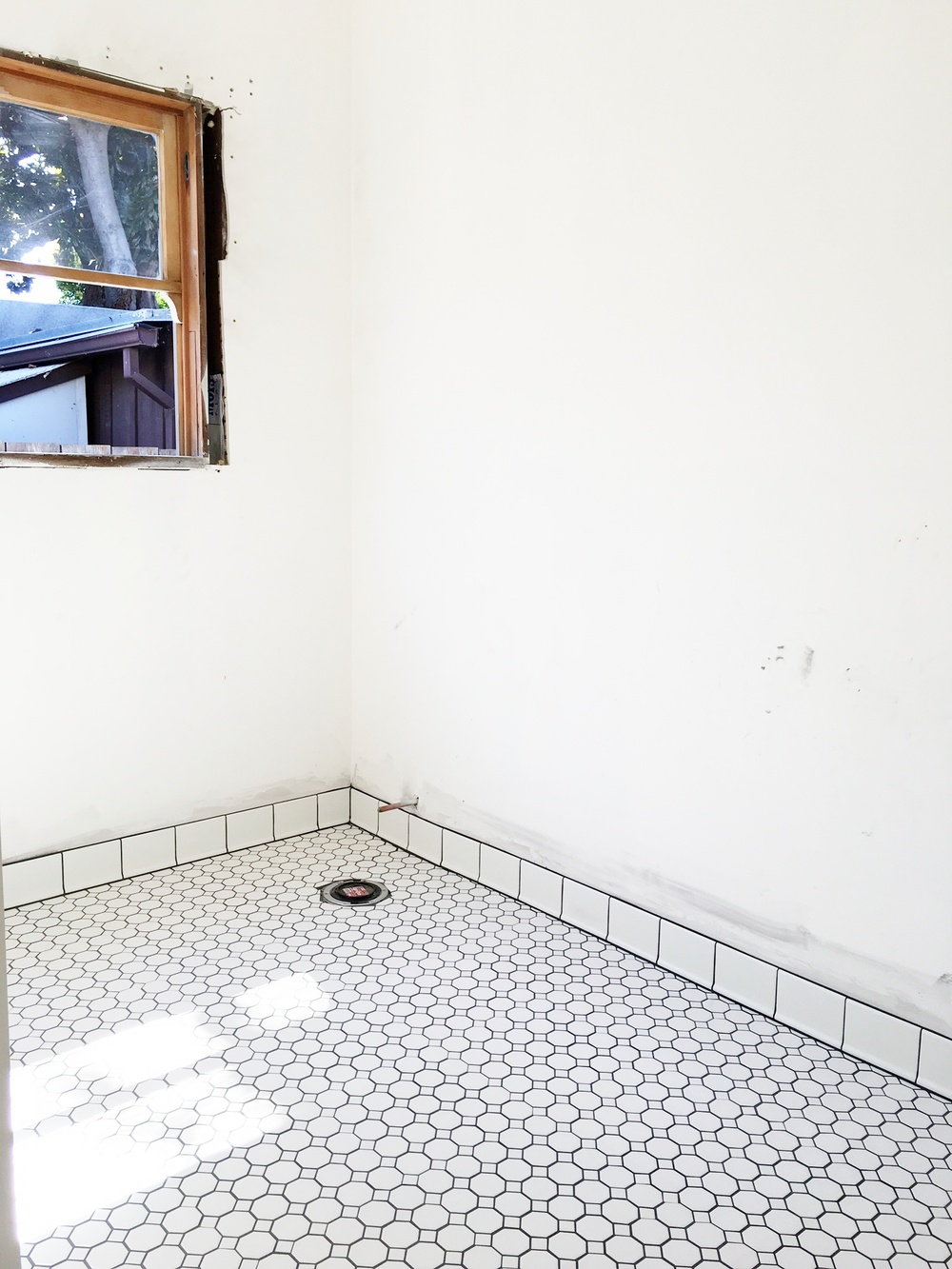 The floor tile is in. We chose a white hexagonal pattern with very dark gray grout. Lookin' good! Next: Installing the vanity and my fun job of restoring the claw foot tub. Ugh.
