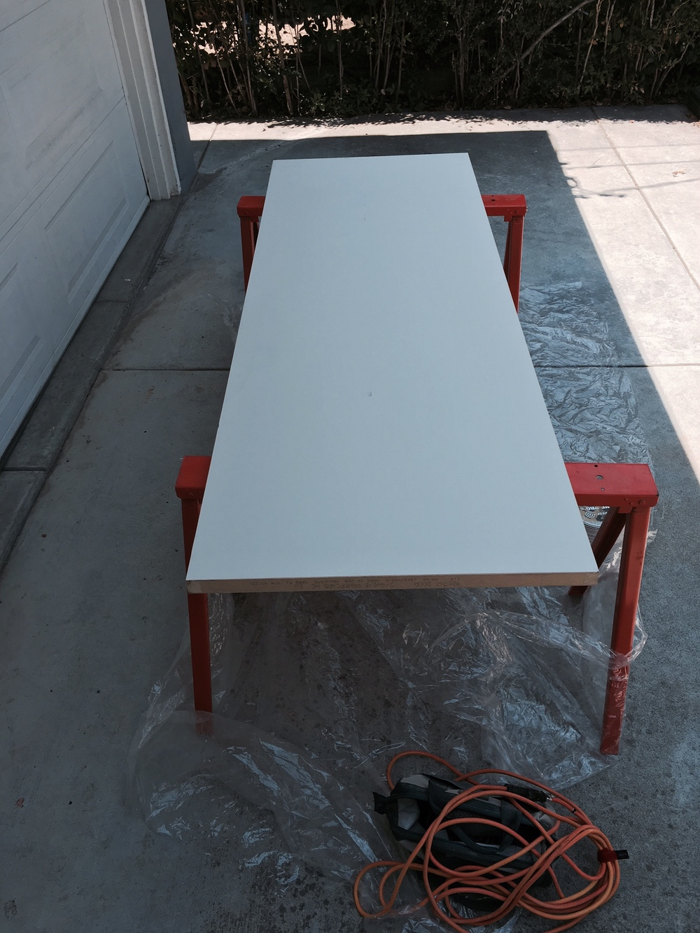 The easiest way to paint or sand any object is to raise it onto a table. I used these portable saw horses and tried to keep it in the shade.