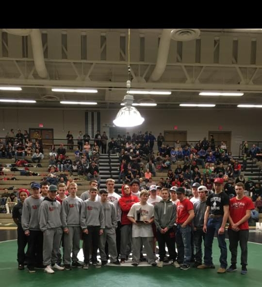 Freshman Cody Brewer is pictured with his team while he holds the Ute's trophy for their weekend win. The Uintah Ute wrestling team won 1st place at the Thoman Soda Ash Memorial tournament. Cody Brewer stepped up to Varsity and wrestled up two weight classes, winning a key match that opened the way for the Ute win.