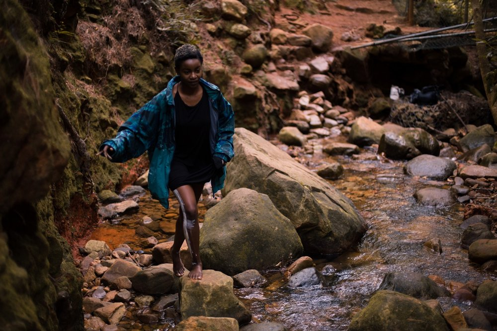girl_crossing_hiking_river_pebbles