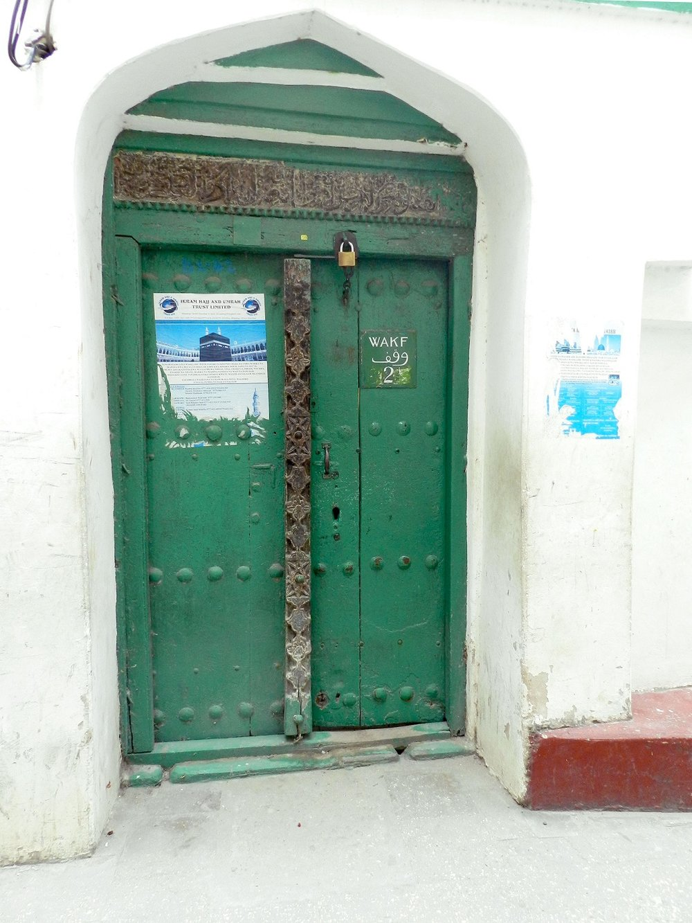 A Green Arab-style door with Qur'an verses inscribed above it