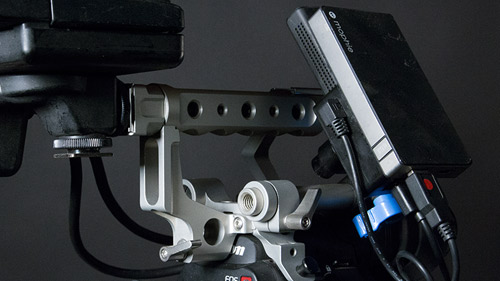 Transmitter attaches to C300's top handle, and also uses USB battery (2.5 hrs). You can optionally power the transmitter from a larger gold-mount (Anton Bauer) battery attached to back of camera .