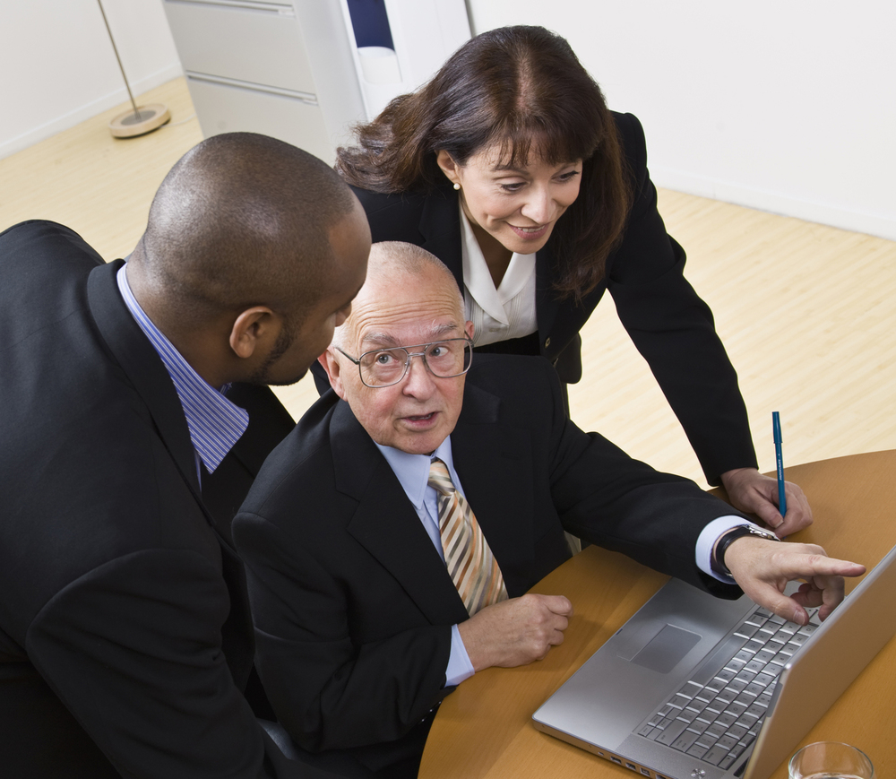 Image of black male attorney, white male attorney and white female attorney grouped around a laptop..  desert adr.
