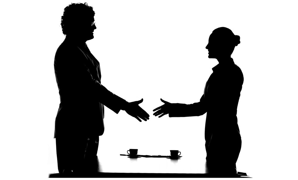 Image of male attorney and female attorney reaching out to shake  hands across the table.  Desert ADR.