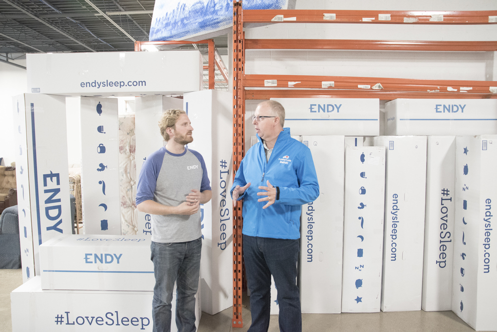 Dan Kershaw, Executive Director of Furniture Bank - Toronto, and Endy Sleep CEO Mike Gettis converse during the mattress company's visit to the charitable furniture store.