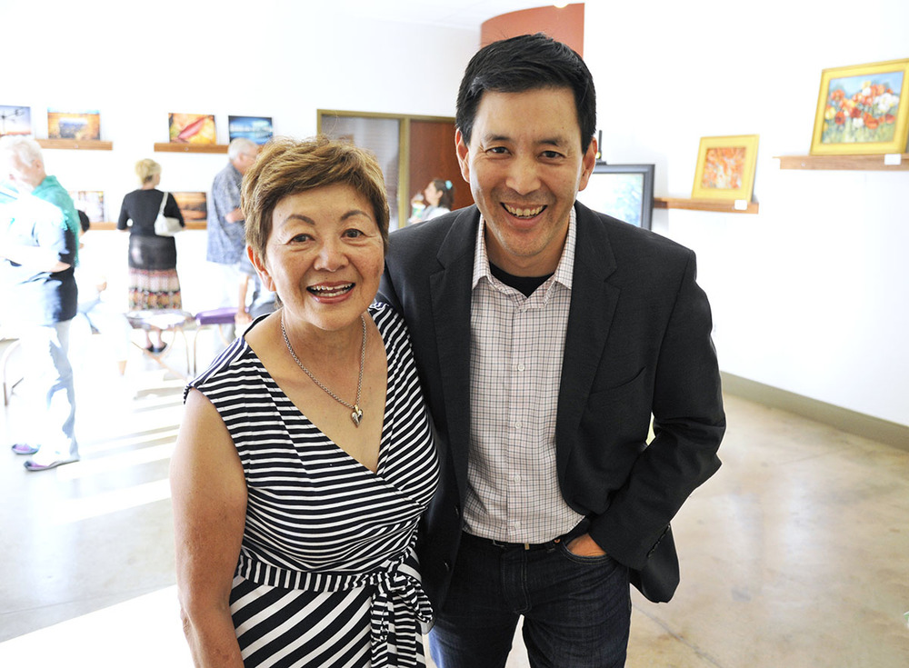 Painter Tomiko Watada Takeda stands with her son art photographer Scott Takeda at their joint art show at the IDEA Place Gallery in Rocky Ford, Colorado. (July 2015)