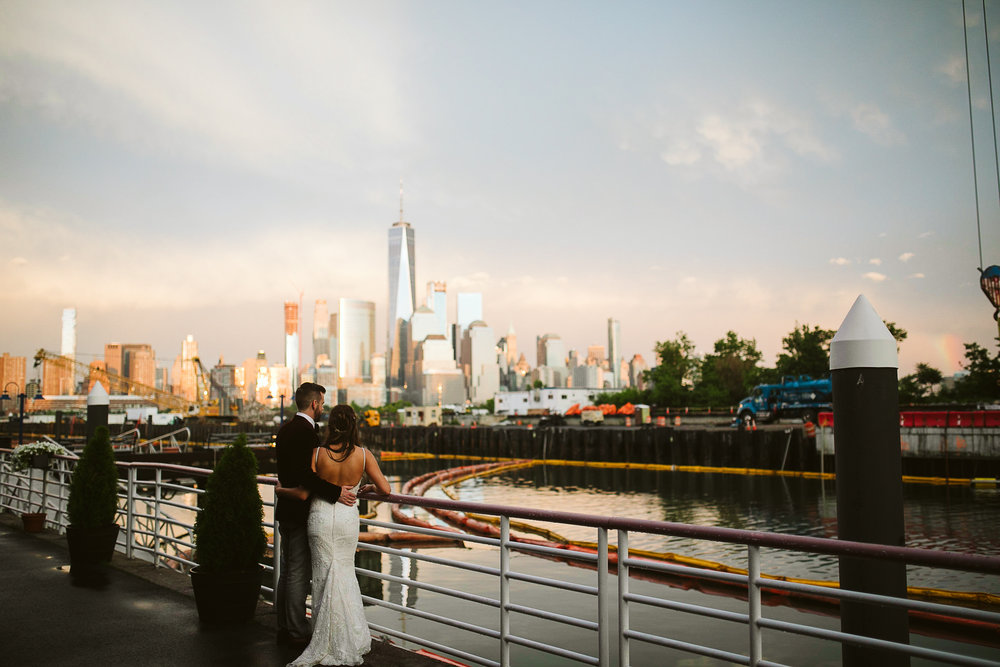 The bride and groom portrait with NYC and the bay at sunset at this Battello Wedding in Jersey City, NJ